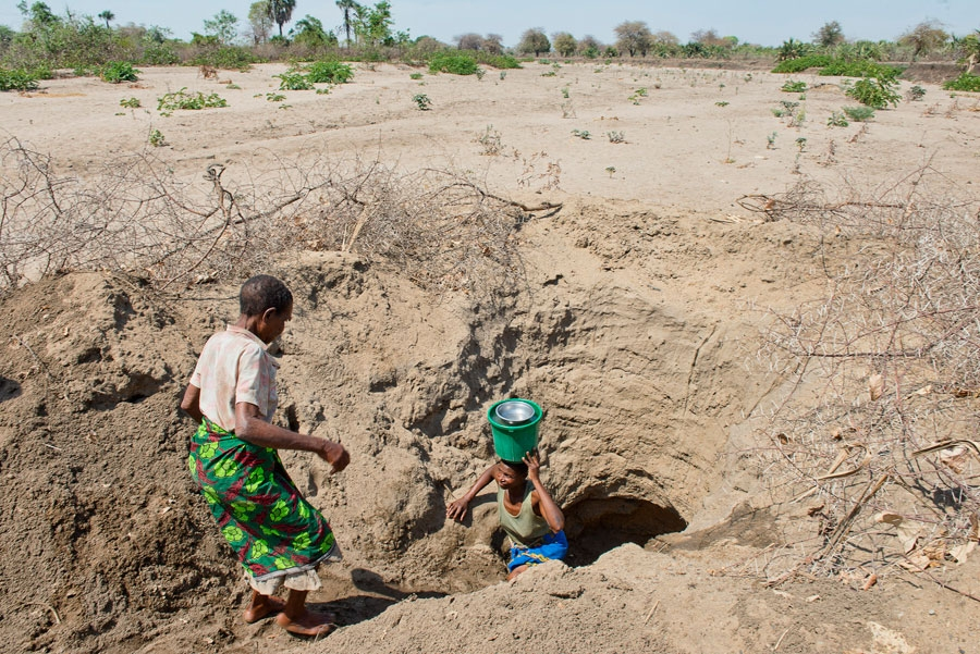 <p>Women fetch water from an open well under a dried river bed in the Chikwawa district of Malawi.</p>