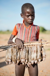 <p>A young boy with his catch of rats in the Karamoja region of Uganda</p>