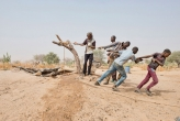 <p>Men pull a rope to raise water from well near Zinder, Niger.</p>