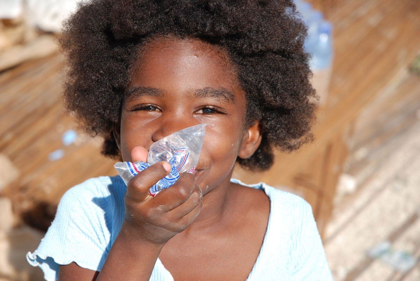 <p>A young girl drinks clean water from a bag supplied by the Haiti Red Cross following three successive hurricanes in a week that left her homeless.</p>