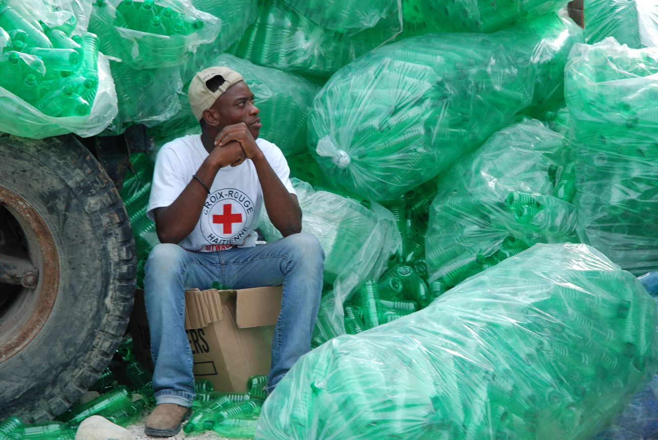 <p>A Haiti Red Cross volunteer waits to deliver bottled drinking water  following three successive hurricanes in a week in 2008.</p>