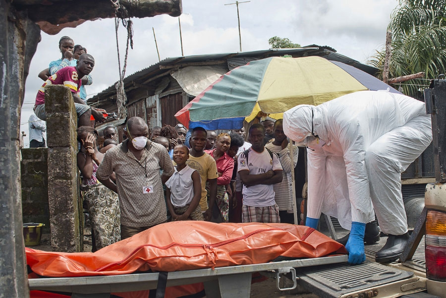 <p>A Red Cross burial team removes a body from a home in Monrovia, Liberia</p>
