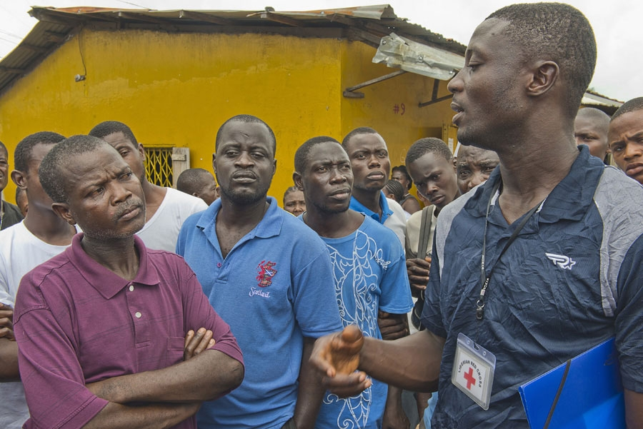 <p>A Red Cross burial team leader talks for relatives and neighbors about removing a body, thought to be an Ebola victim, from a community in Monrovia, Liberia.</p>