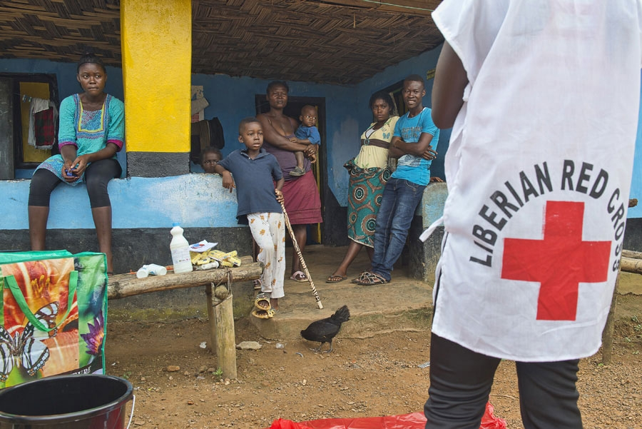<p>A Red Cross volunteer explains to members of a quarantined household how best to protect themselves and get help if one of them becomes sick with Ebola</p>
