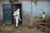 <p>A member of a Red Cross burial team enters a home in Monrovia, Liberia during the 2014 Ebola epidemic</p>