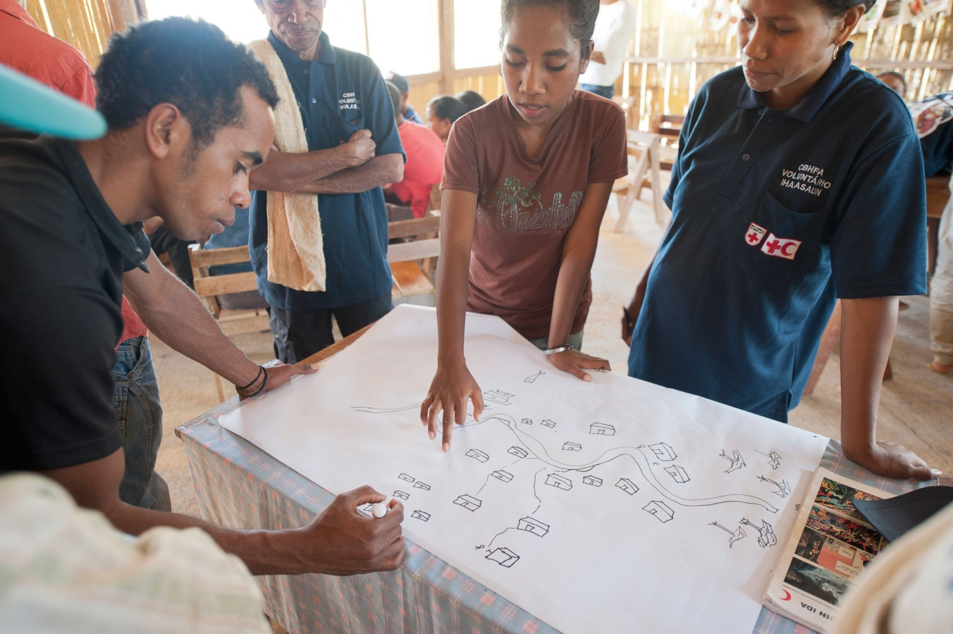 <p>Red Cross volunteers help locals map their village a part of an IFRC Community Based Health program</p>