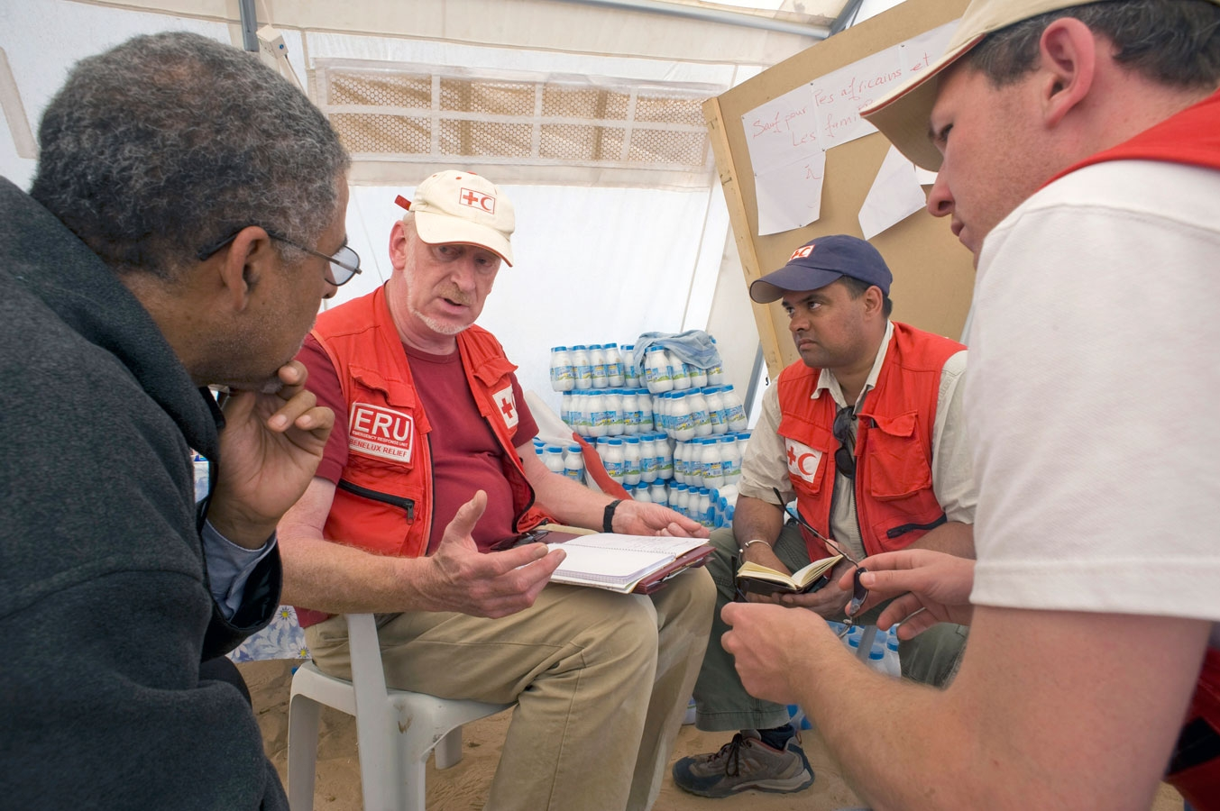 <p>IFRC and Tunisia Red Crescent personnel in a transit camp in Tunisia discuss how to feed the growing number of refugees fleeing civil war in Libya.</p>