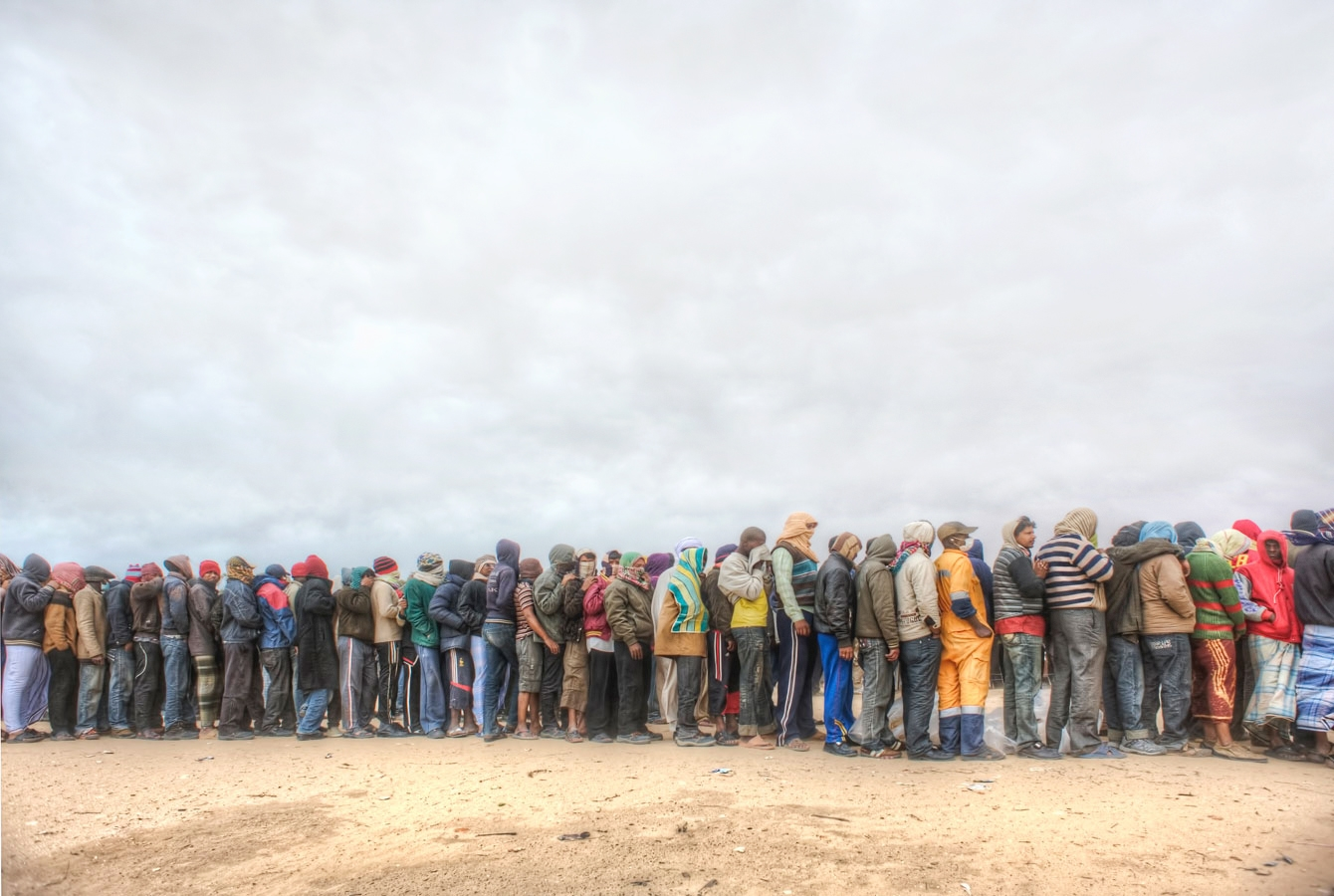 <p>Refugees fleeing civil war in Libya queue for food in the transit camp near the Tunisian border</p>
